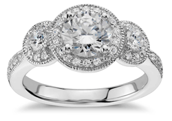 three stone engagement ring with millgrain detail halo