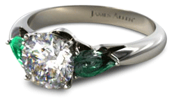 three stone diamond engagement ring with pear shaped emerald side stones